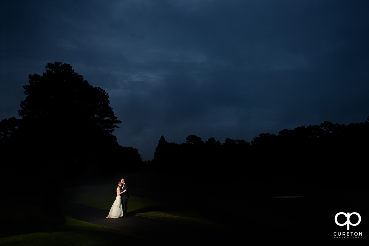 Epic shot of a bride and groom on the golf course at twilight at the wedding reception at Spartanburg Country Club.