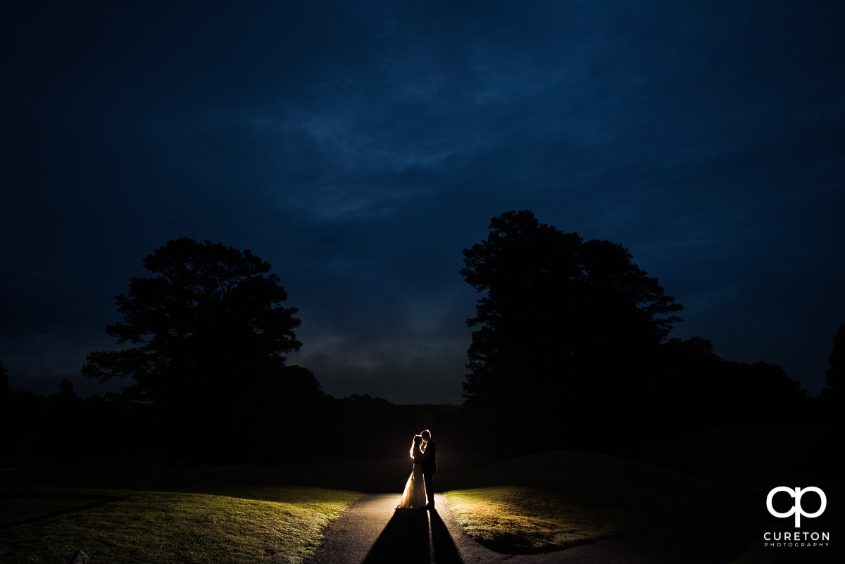 Bride and groom underneath a deep blue sky at night on the golf course at the wedding reception at Spartanburg Country Club.
