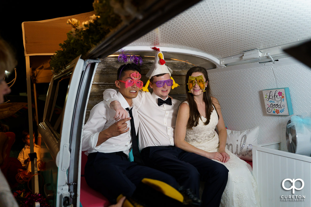 Bride and groom enjoying a photo booth in a Volkswagen bus.