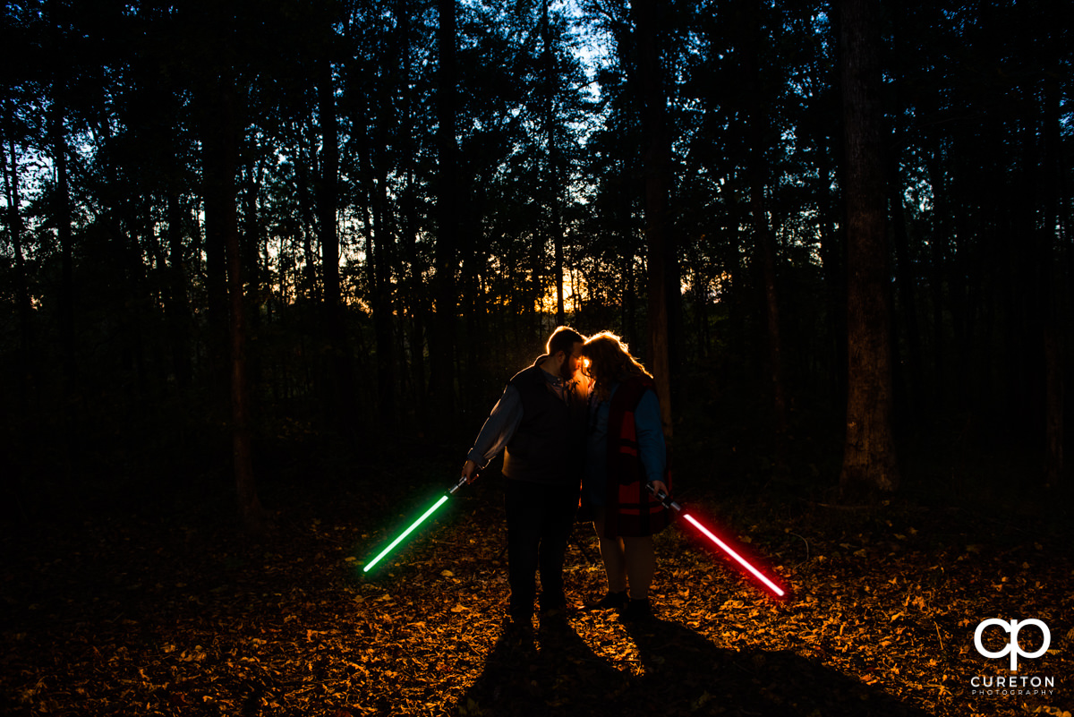 Future bride and groom holding lightsabers in the forest at their Star Wars themed engagement session.