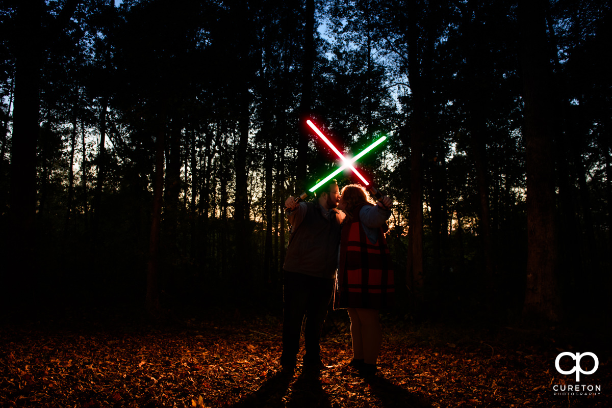 Bride and groom crossing lightsabers at their Star Wars engagement session.