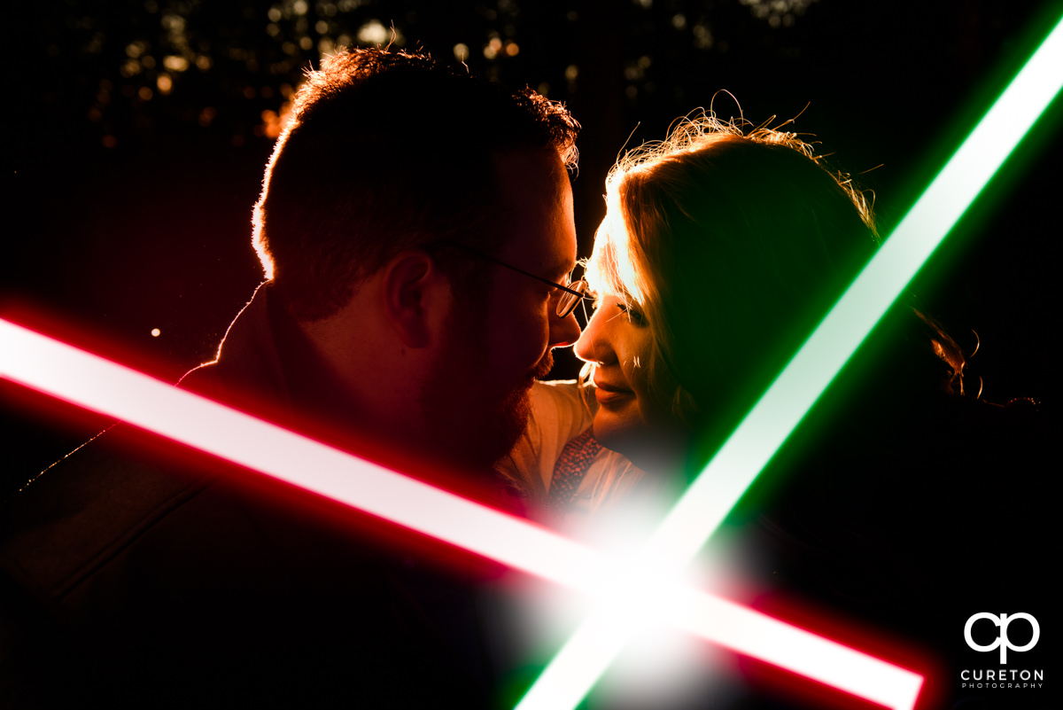 Bride and groom nose to nose with crossing lightsabers at their Star Wars engagement session.