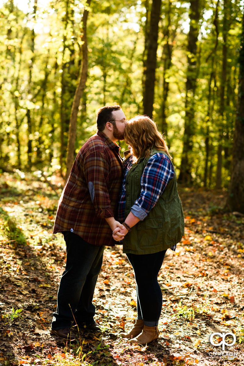 Groom kissing his bride on the forehead in the forest at their engagement session.