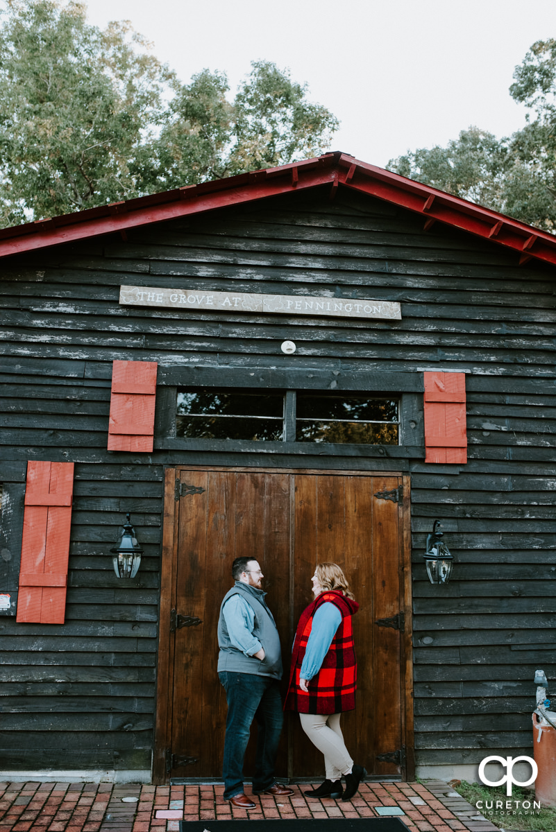 Bride and groom leaning on a rustic barn.