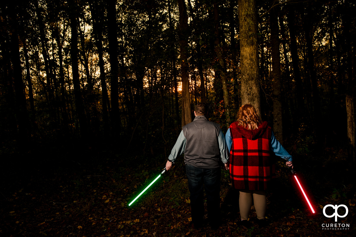 Engaged couple holding lightsabers at their Star Wars engagement session.