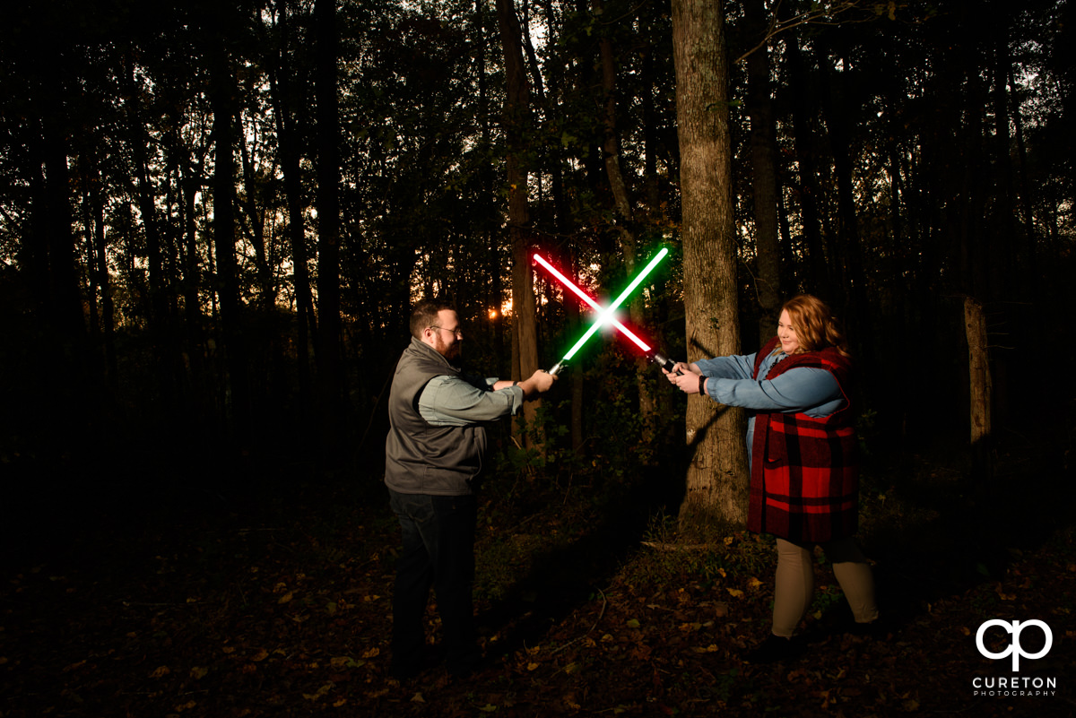 Future bride and groom battling with lightsabers at their Star Wars themed save the date session.