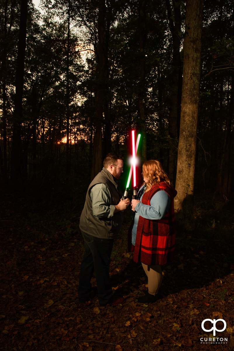 Engaged couple crossing lightsabers.