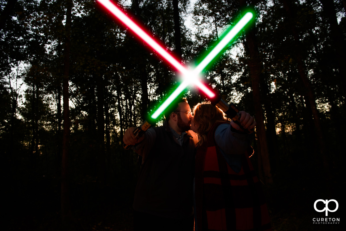 Future bride and groom kissing behind lightsabers at their Star Wars engagement session.