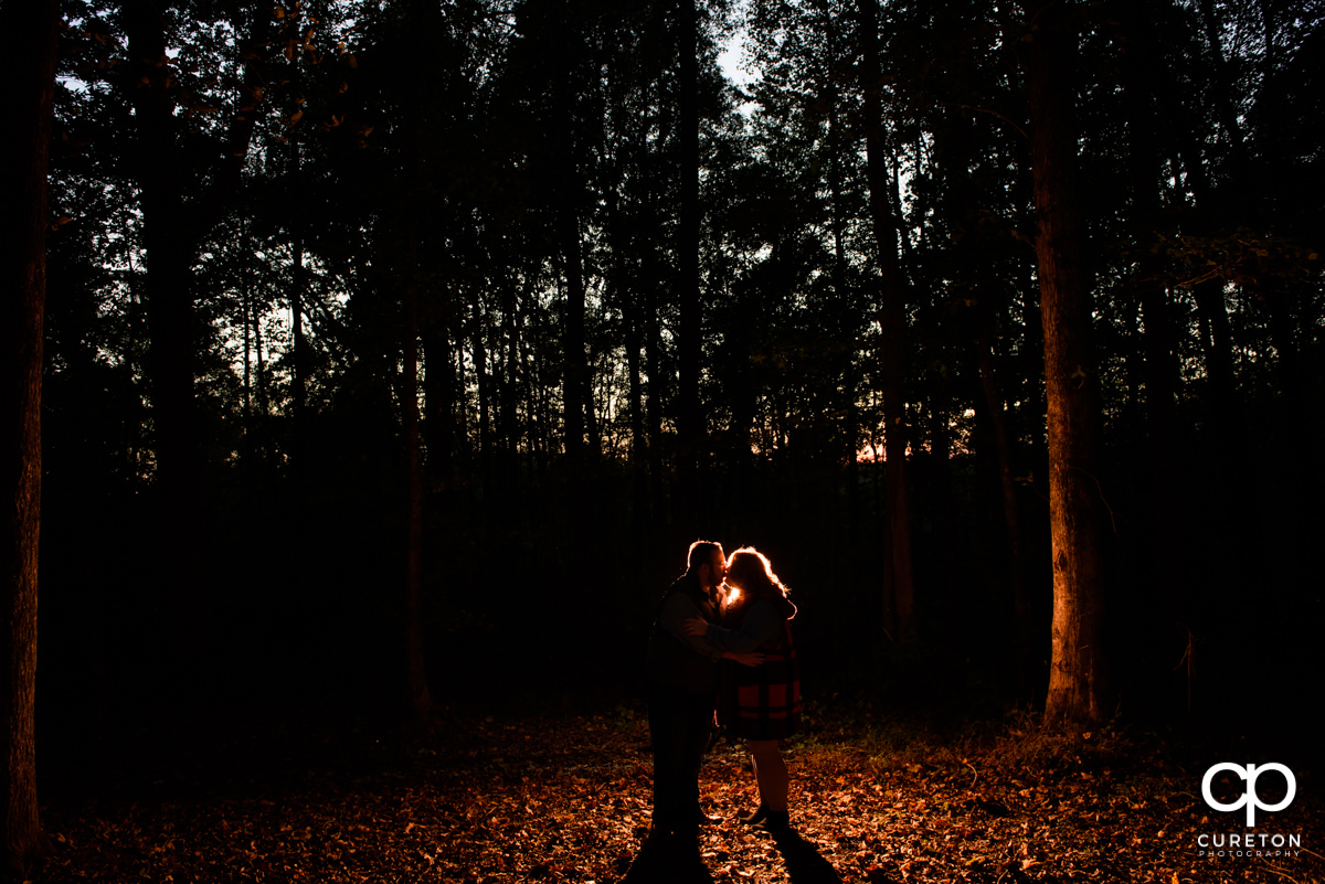 Engaged couple walking in the forest at sunset.