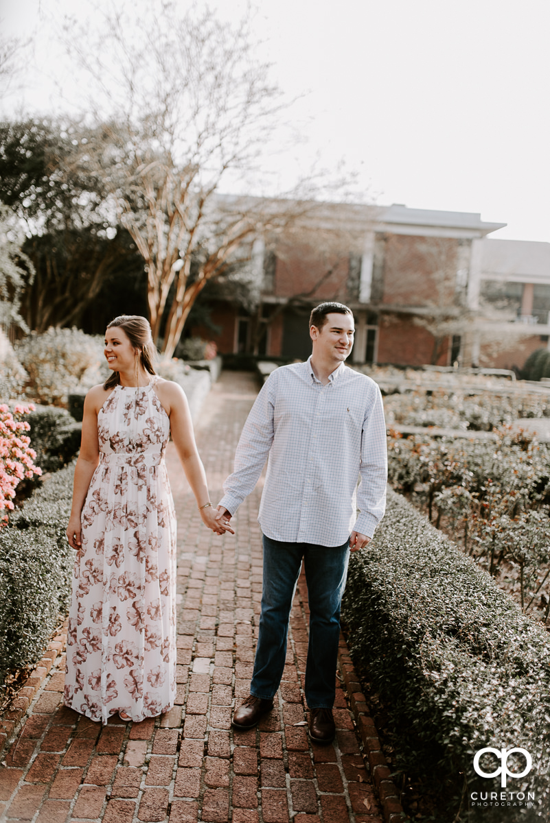 Future bride and groom in a rose garden in Greenville,SC during an engagement session.