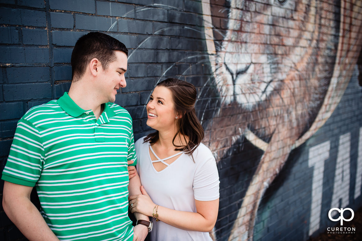 Future bride and groom outside of the Swamp Rabbit Brewery for their engagement session.