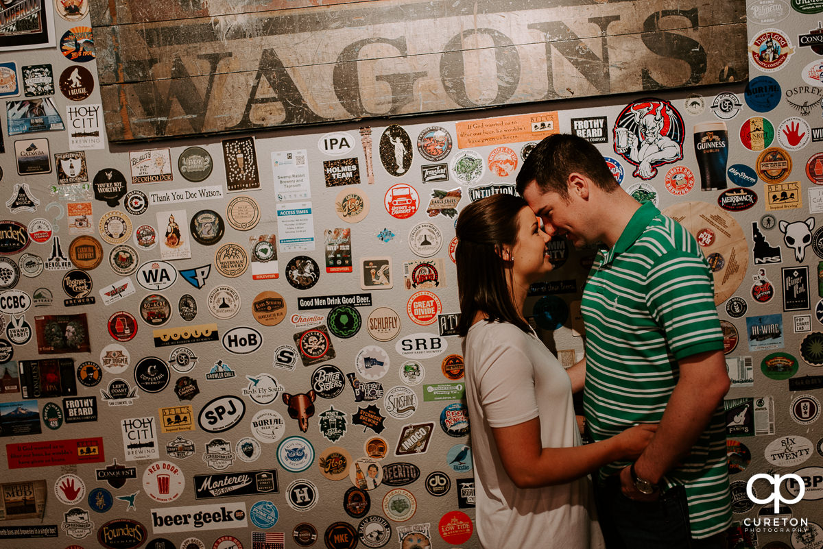 Man and his future bride stanfing in front of a wall of stickers during their Swamp Rabbit Brewery engagement session.