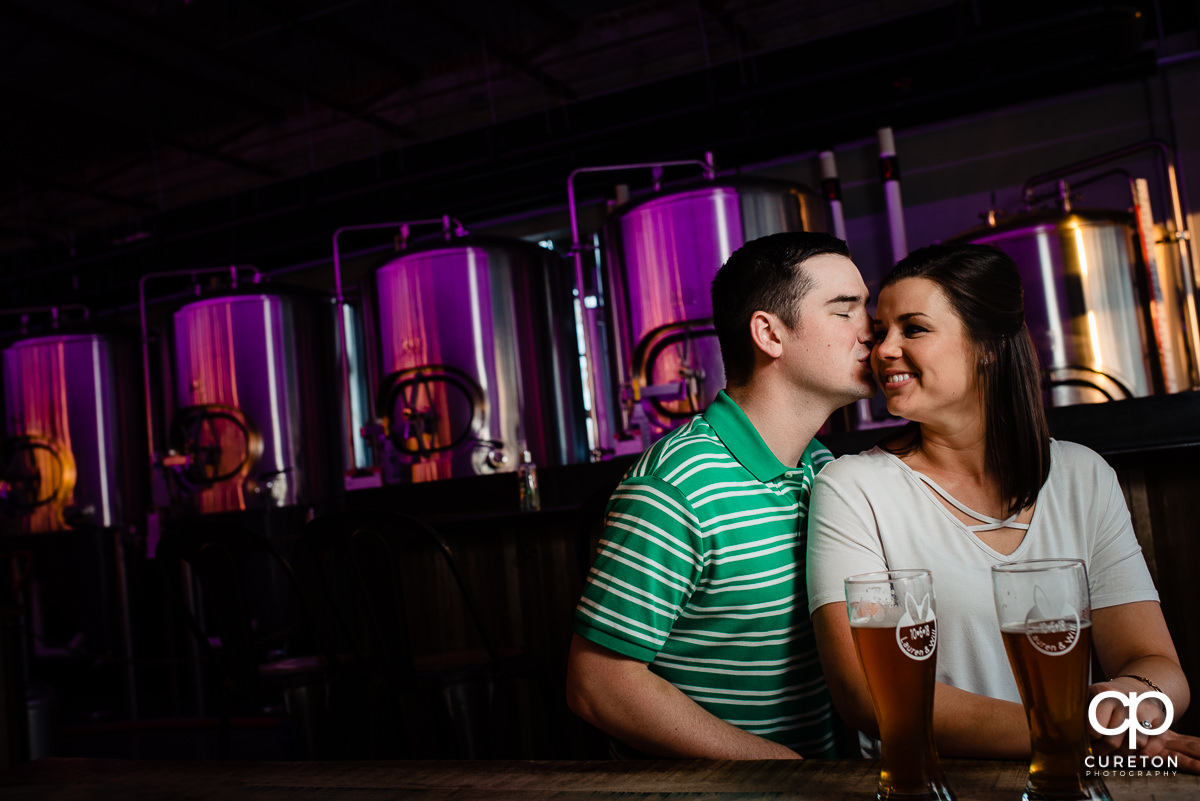 Woman being kissed on the cheek by her future husband during their Swamp Rabbit Brewery engagement session.