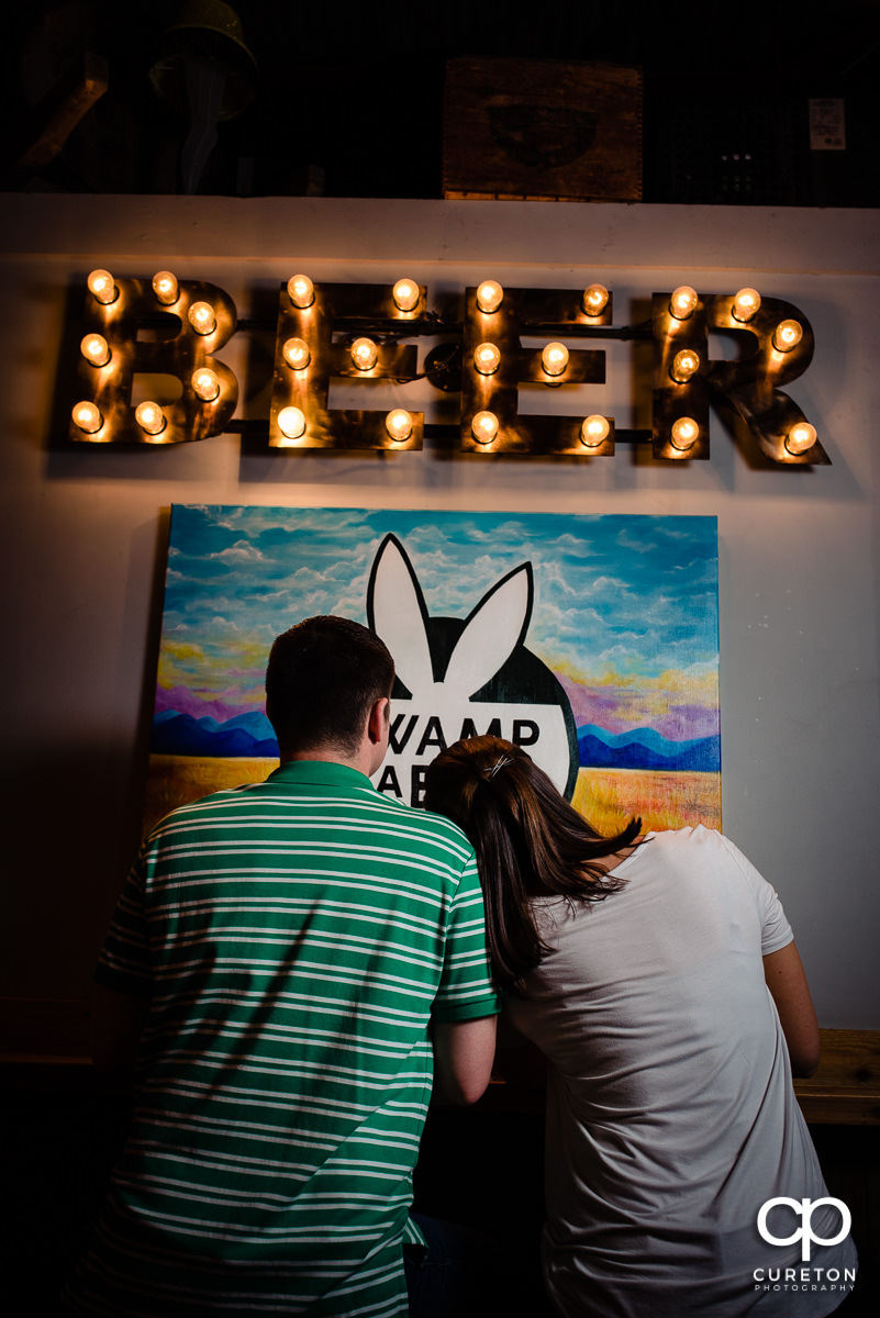 Woman laying her head on her fiancees shoulder as they sit in front of a beer sign during their Swamp Rabbit Brewery engagement session.