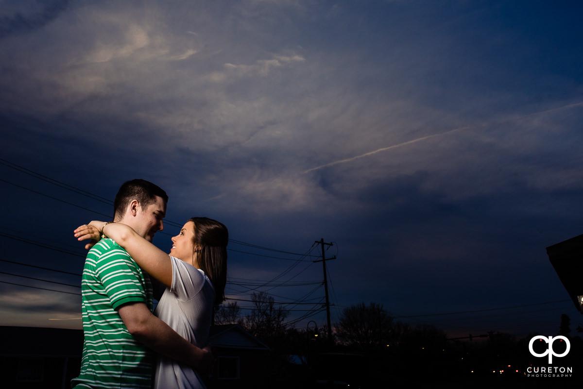 Bride and groom hugging underneath a purple sky.