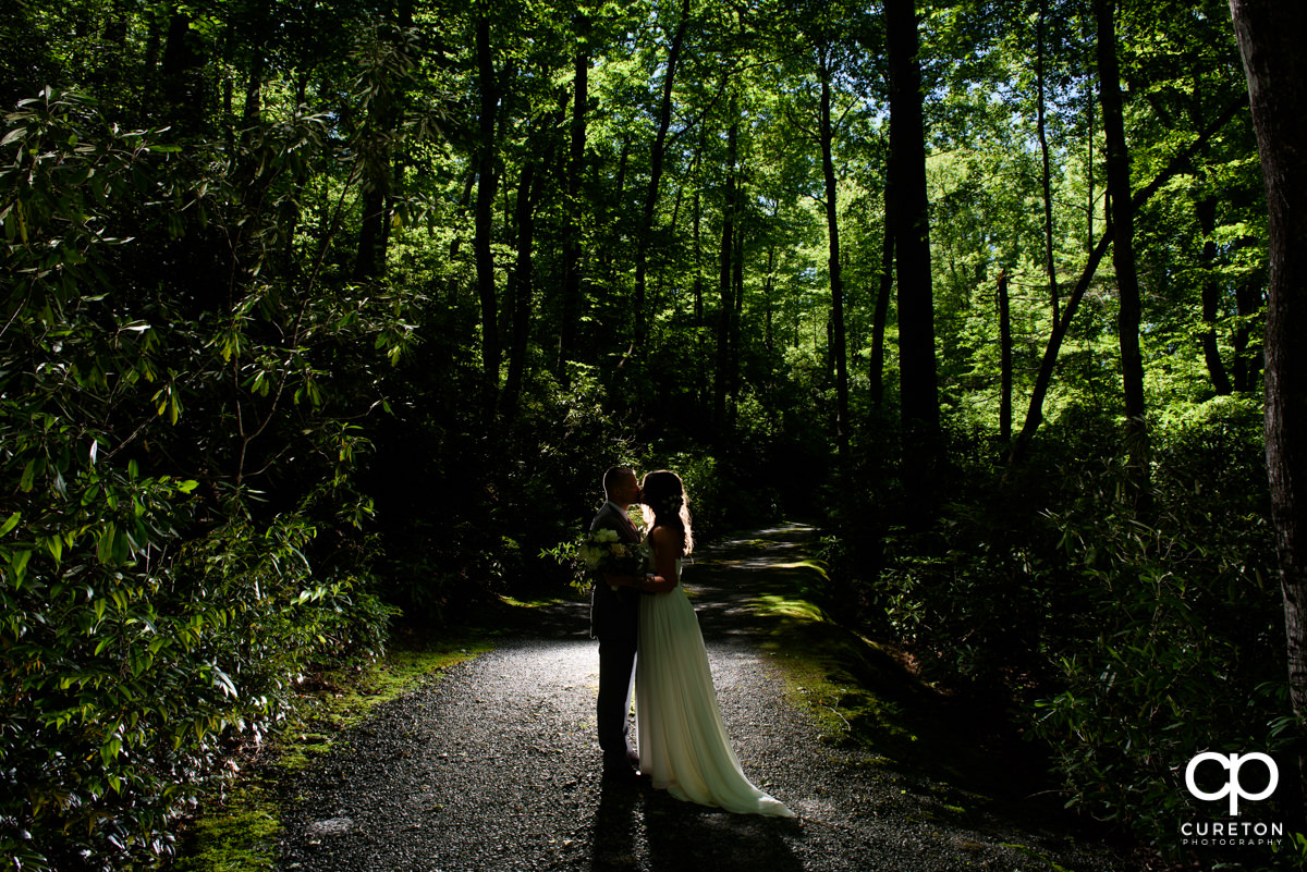 Bride and groom kissing in the forest after their mountain elopement wedding at Symmes Chapel.