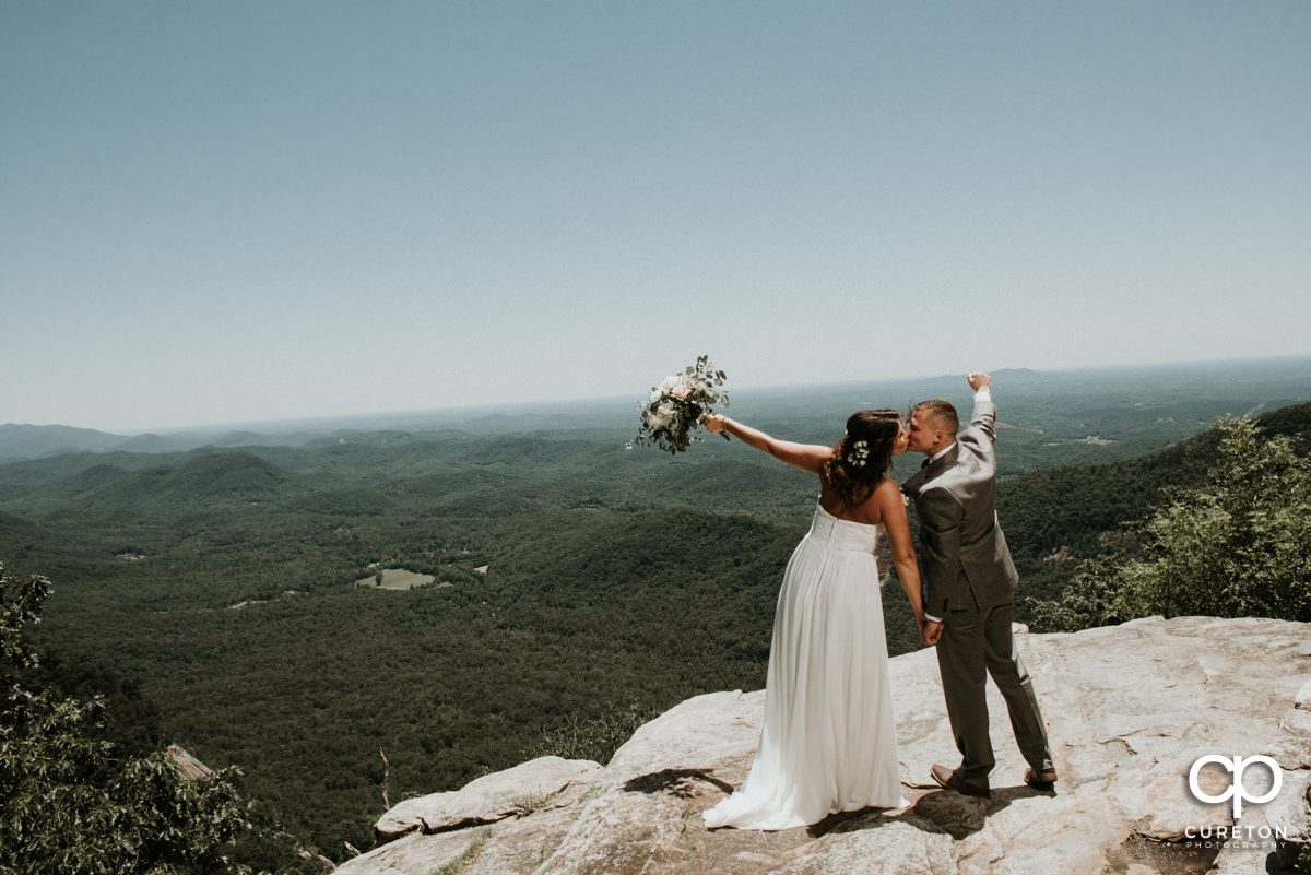 Bride and groom standing on a cliff at Pretty Place after their mountain elopement wedding at Symmes Chapel.