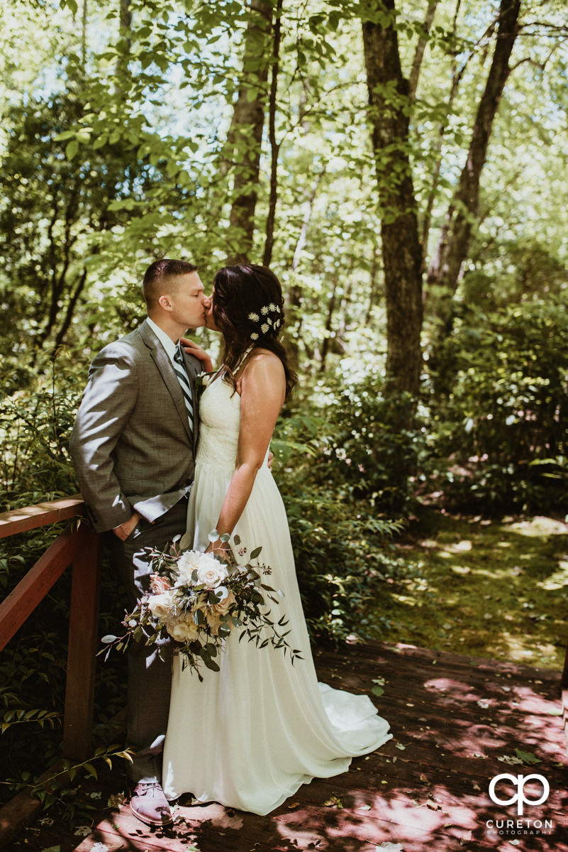 Bride and groom kissing in the forest after their mountain elopement.