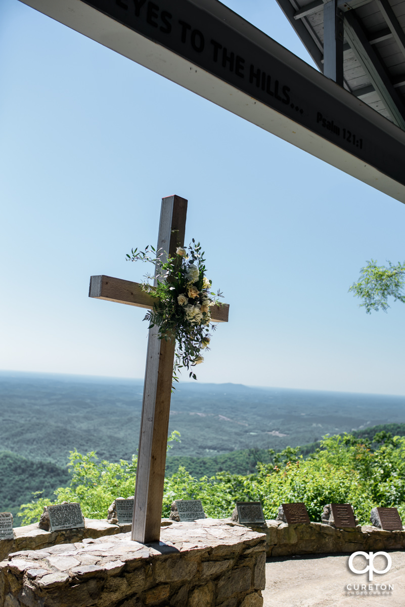 Cross at Pretty Place with flowers placed on it.