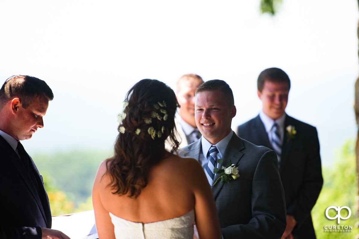Groom smiling at his bride during the Symmes Chapel wedding ceremony.