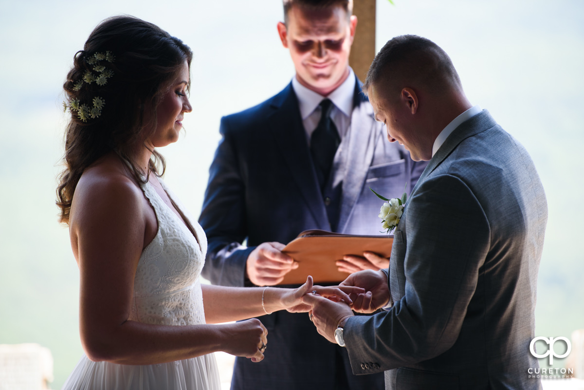 Groom placing the ring on his bride's finger.