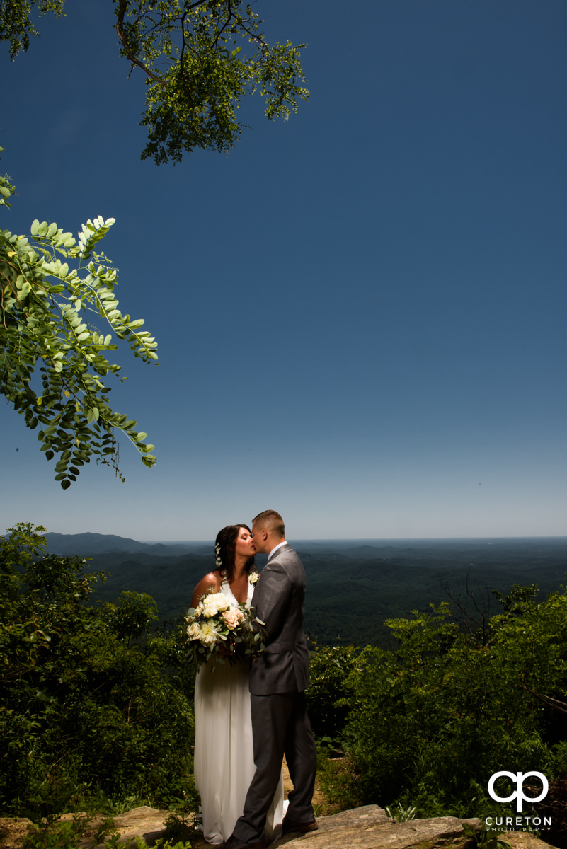 Groom kissing his bride on a mountainside after a Symmes Chapel wedding ceremony.