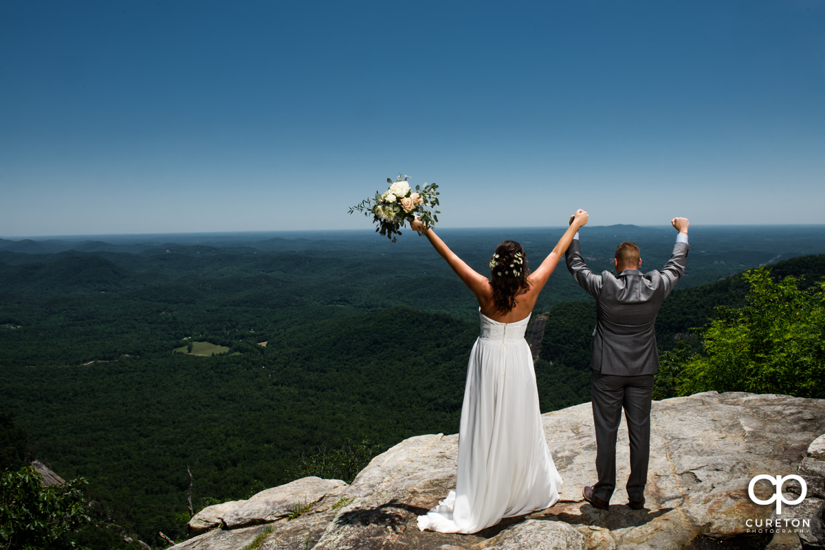 Bride and groom with hands in the air on a cliff at their Pretty Place wedding.