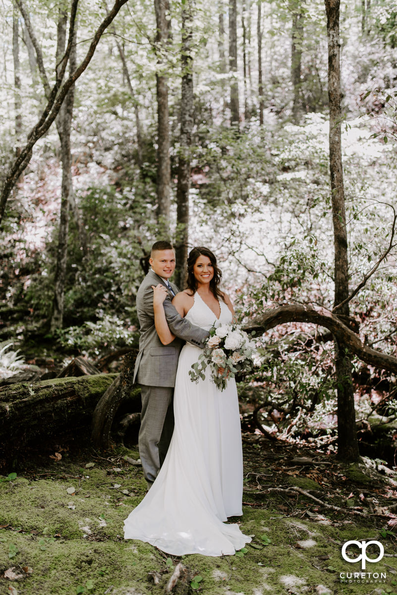 Bride and groom cuddling in the forest.