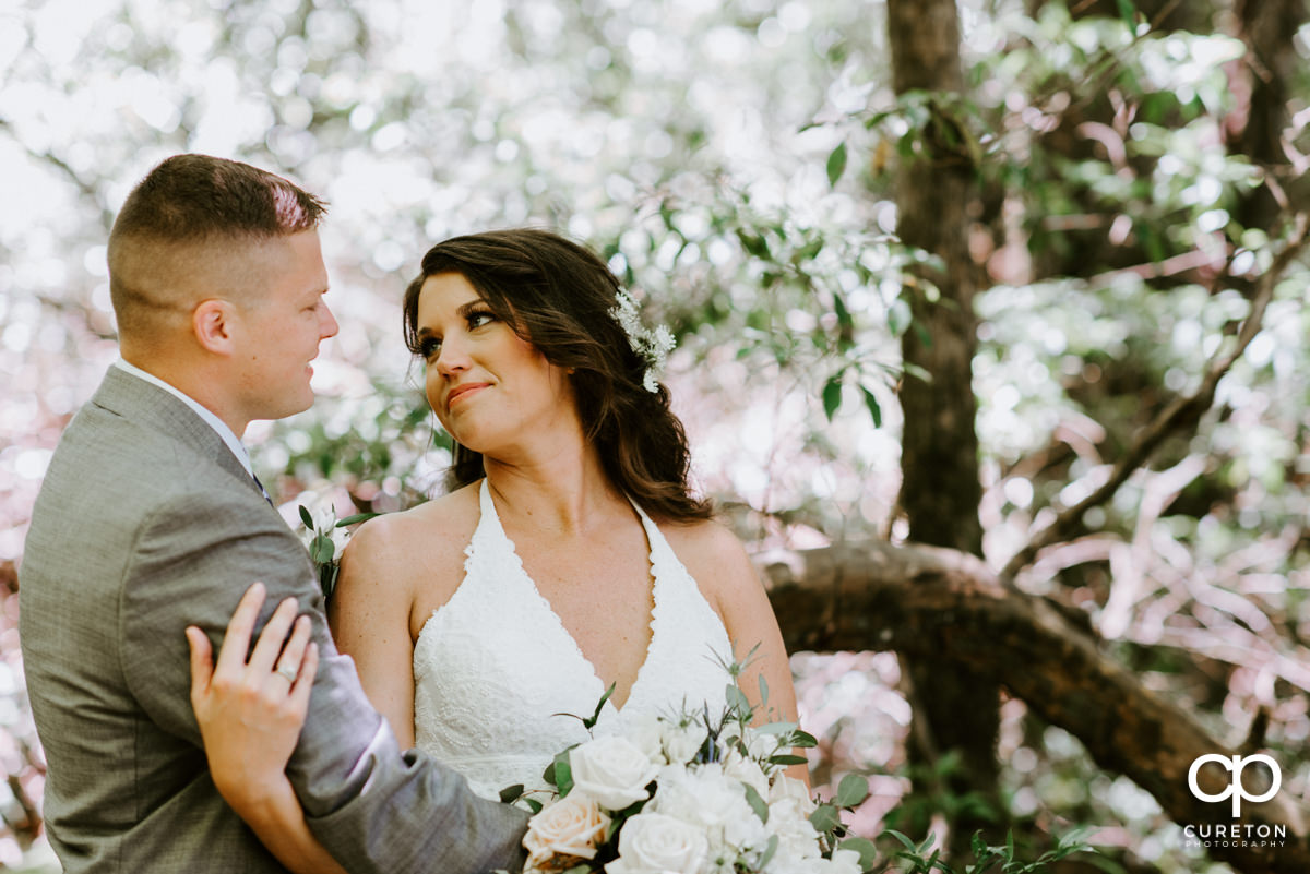 Bride looking at her groom in the forest after their elopement wedding in South Carolina.