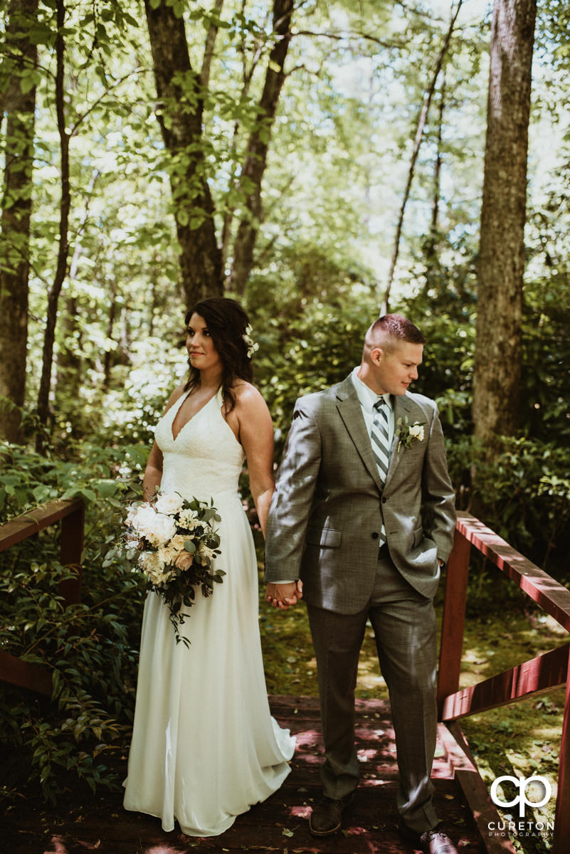 Bride and groom holding hands on a bridge in the woods after their wedding.