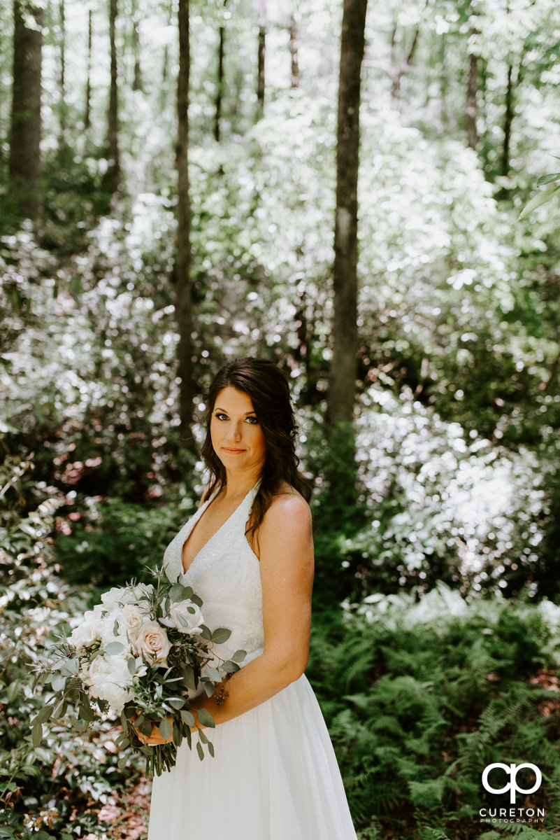 Bride in the forest holding her bouquet.