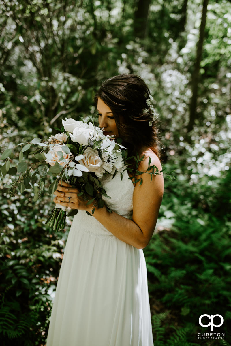 Bride smelling her bouquet of flowers after her wedding.