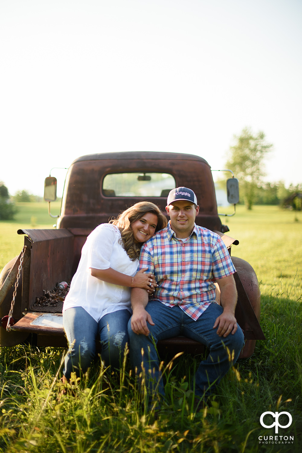 Engaged couple sitting on the tailgate of a vintage truck during a Travelers Rest engagement session.