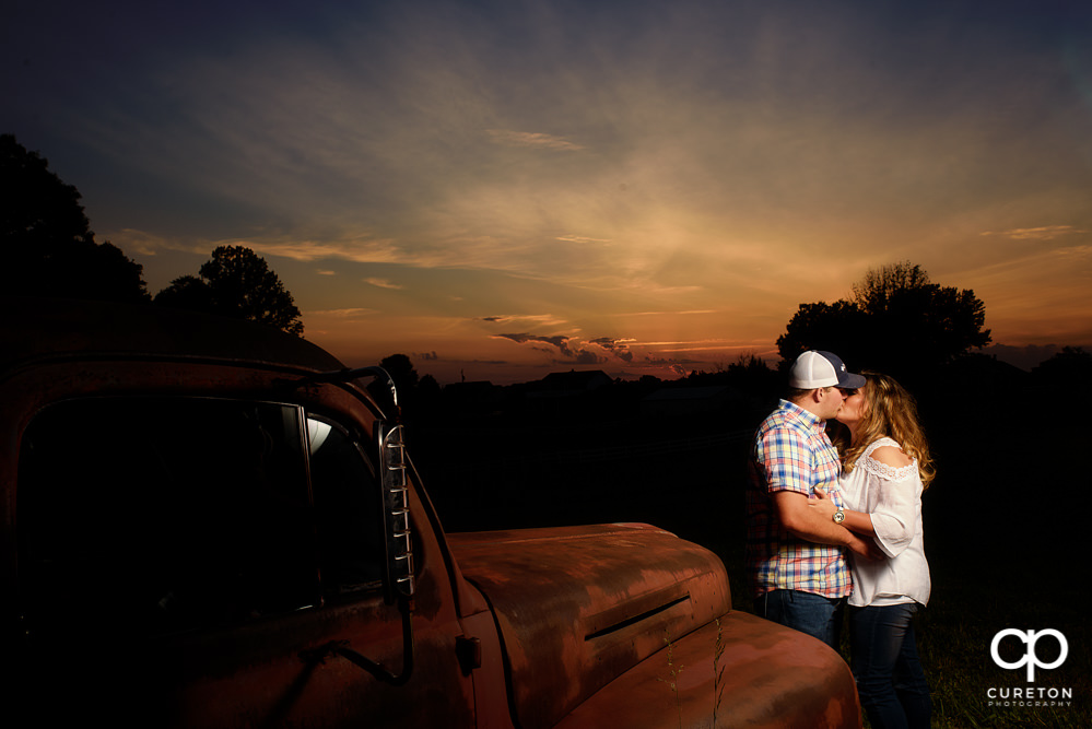 Bride and groom kissing at sunset during a Travelers Rest engagement session..