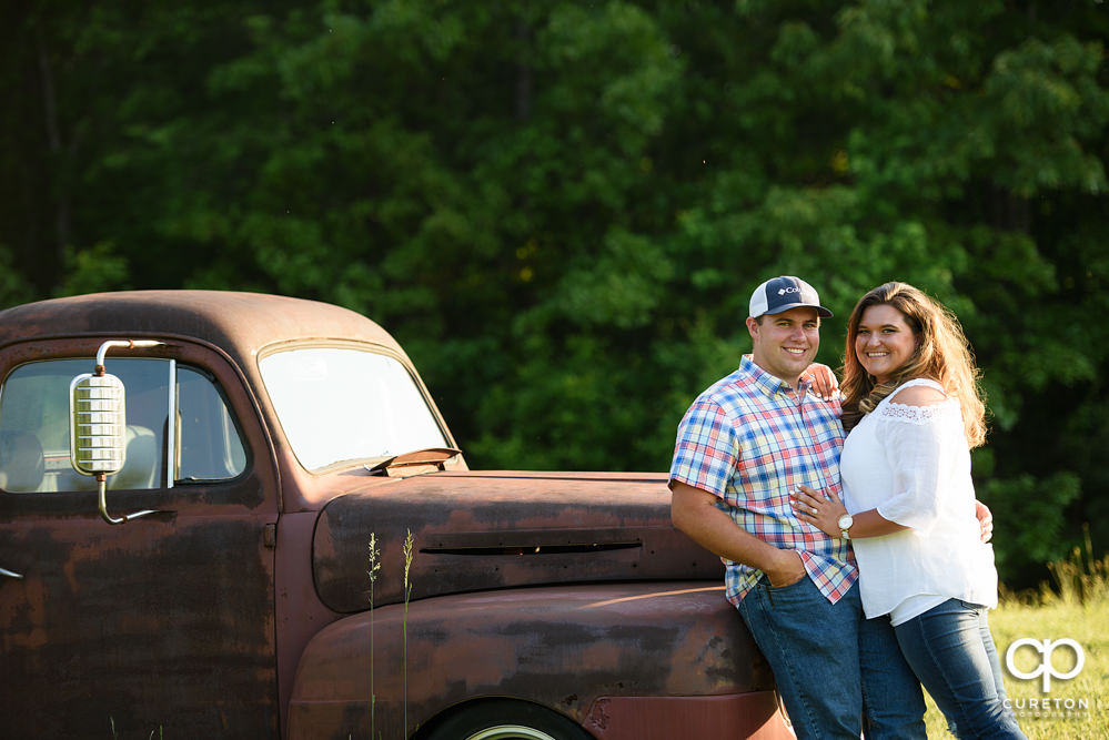 Future married couple leaning on a vintage truck during a Travelers Rest engagement session.