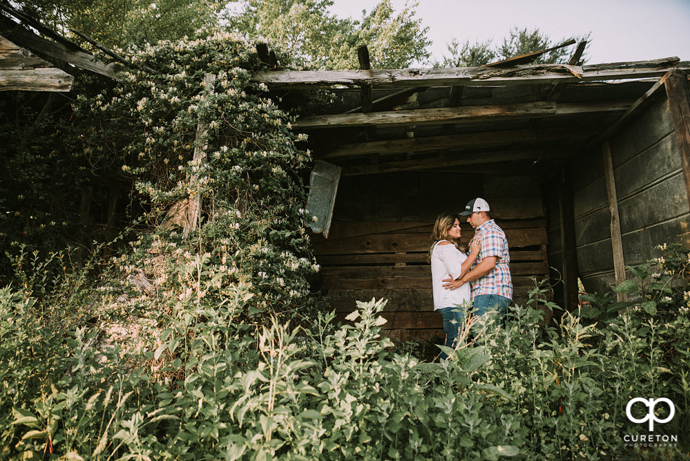 Engaged couple in an overgrown shed during a Travelers Rest engagement session.