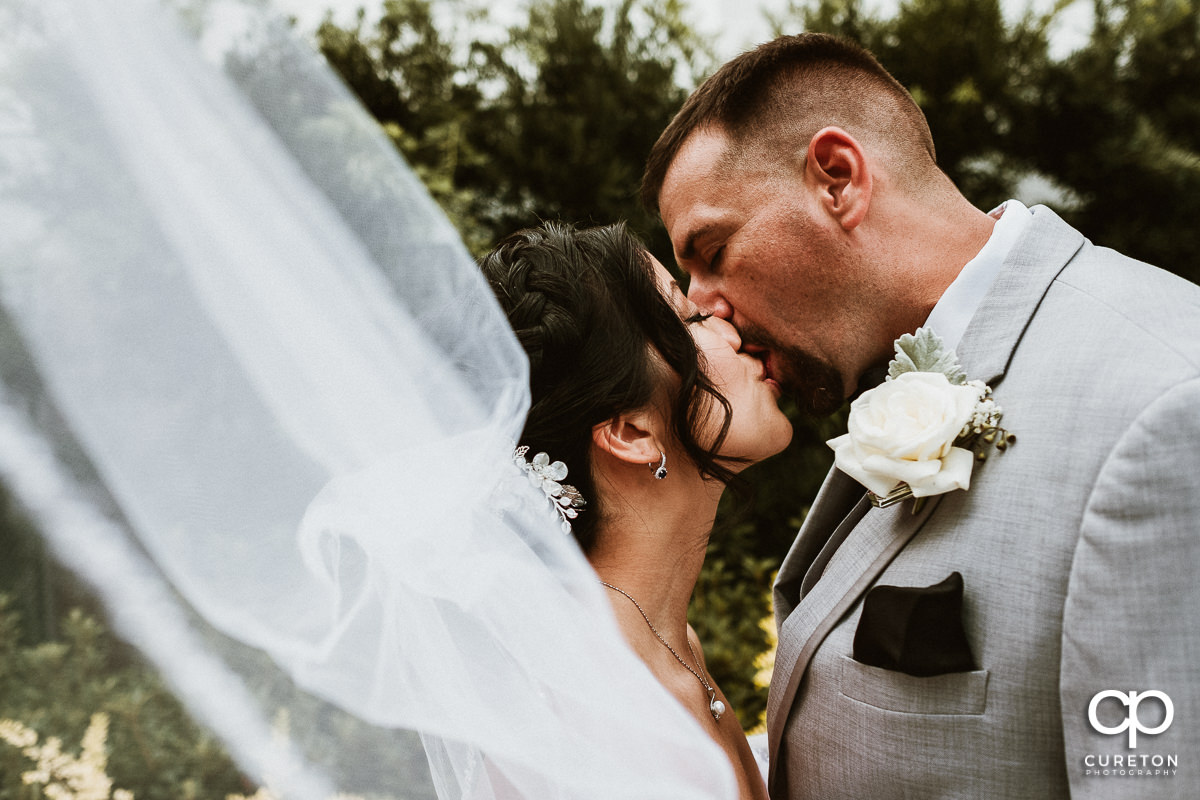 Groom kissing his bride while her veil blows in the wind after their wedding at the Tybee Island wedding chapel .