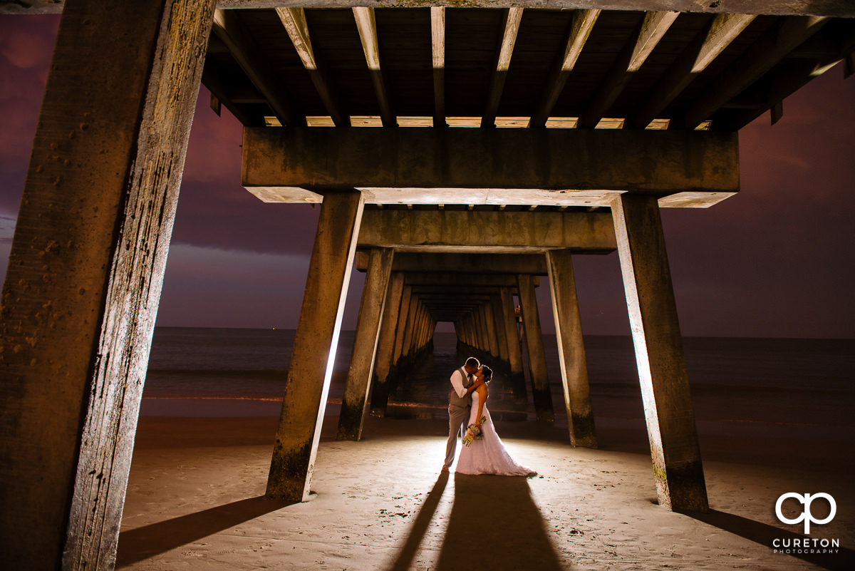 Groom kissing his bride on the beach at sunset underneath the Tybee Island pier after their wedding miles from Savannah,GA .