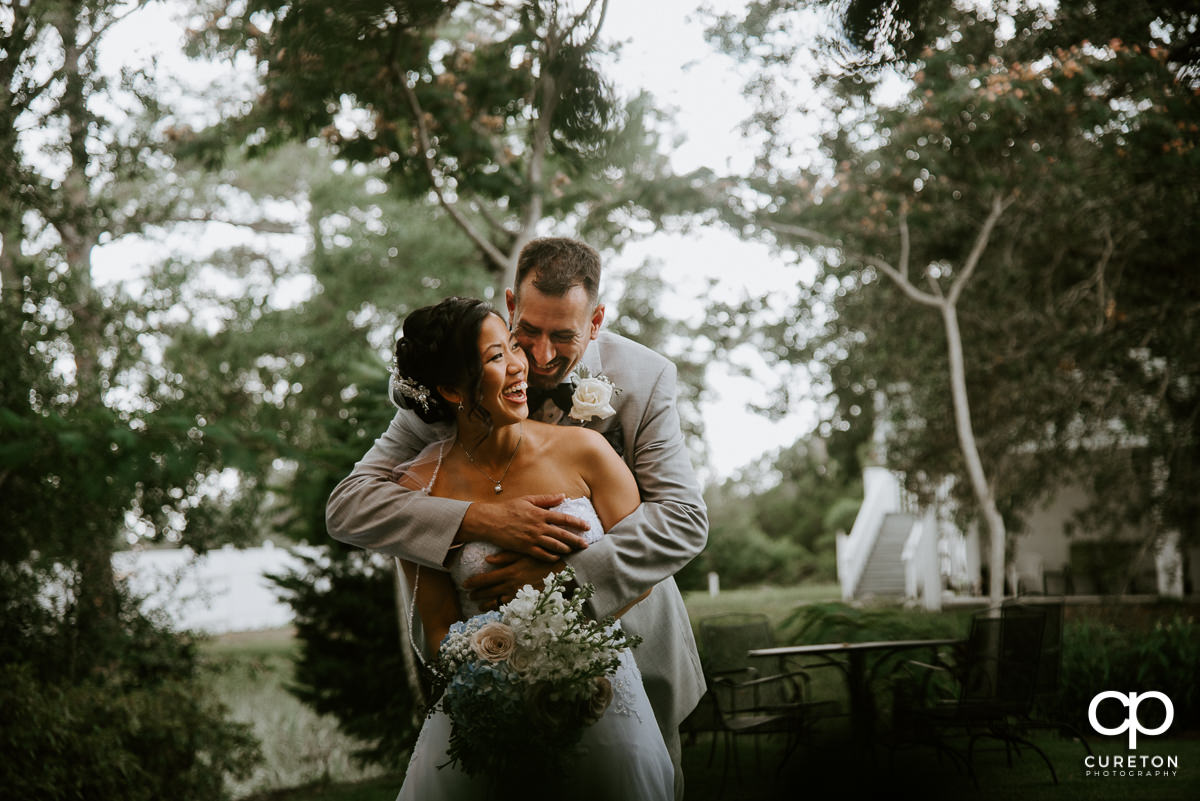 Groom hugging his bride outside the Tybee Island Wedding Chapel after their wedding.