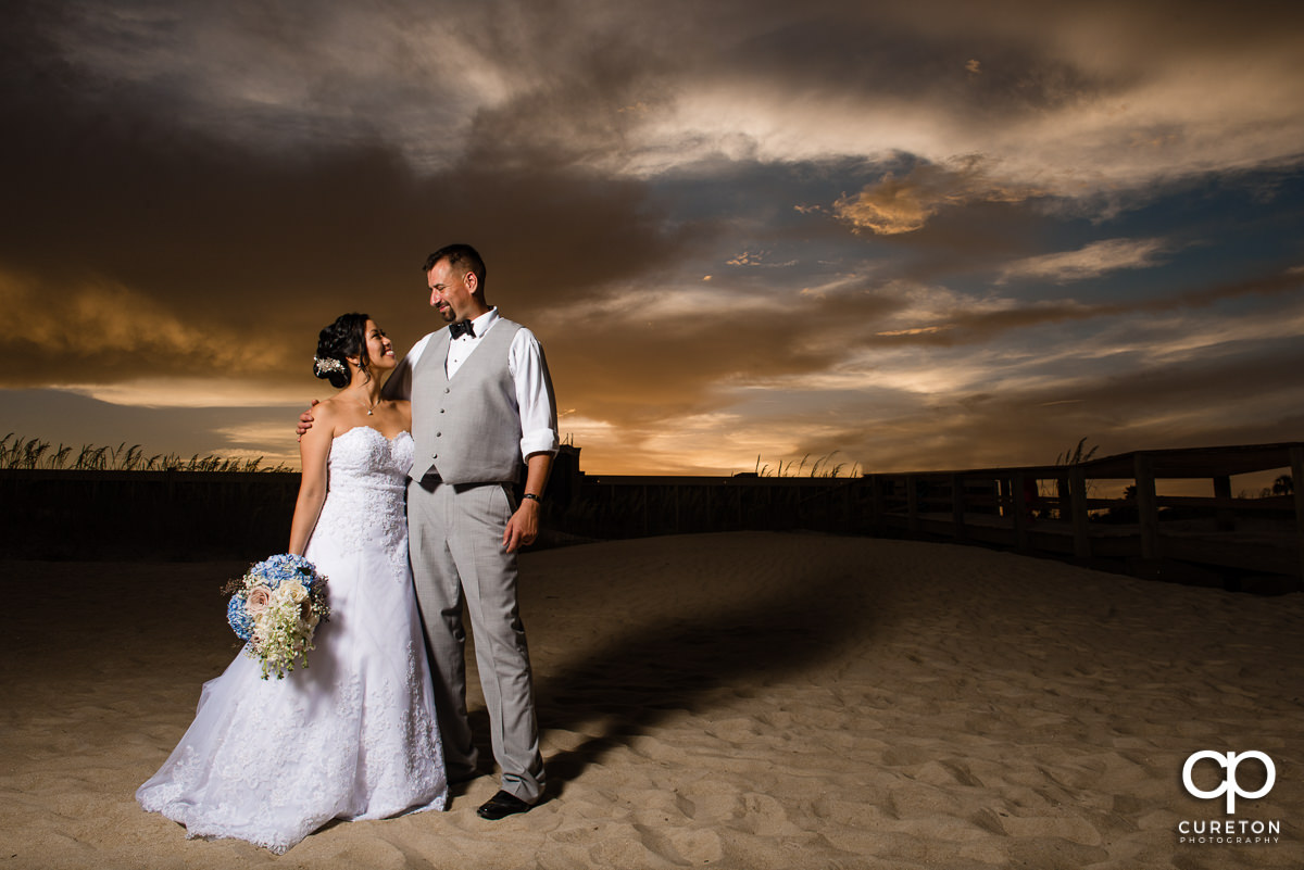 Married couple standing on the beach at sunset after their Tybee Island wedding.