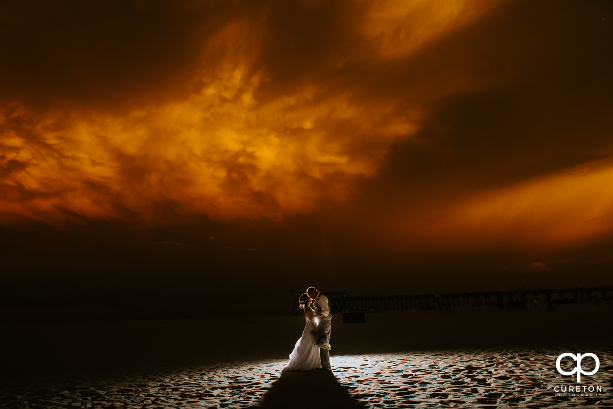 Bride and groom on the beach at sunset after their wedding at the Tybee Island Wedding Chapel.