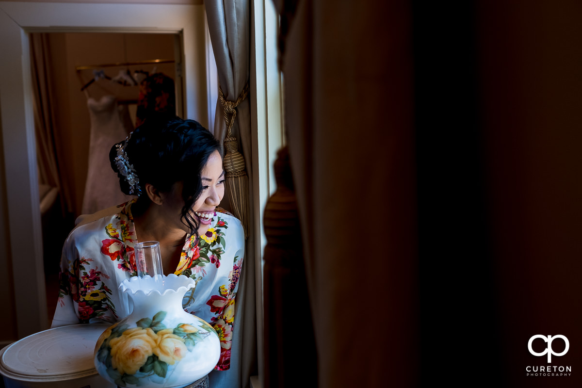 Bride smiling looking out the window before the wedding ceremony in Tybee Island,GA.