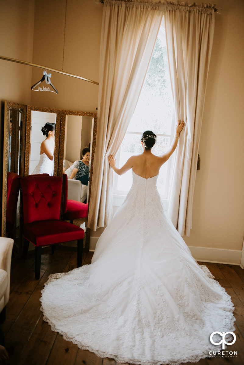 Bride looking out the window showing off the back of the dress.