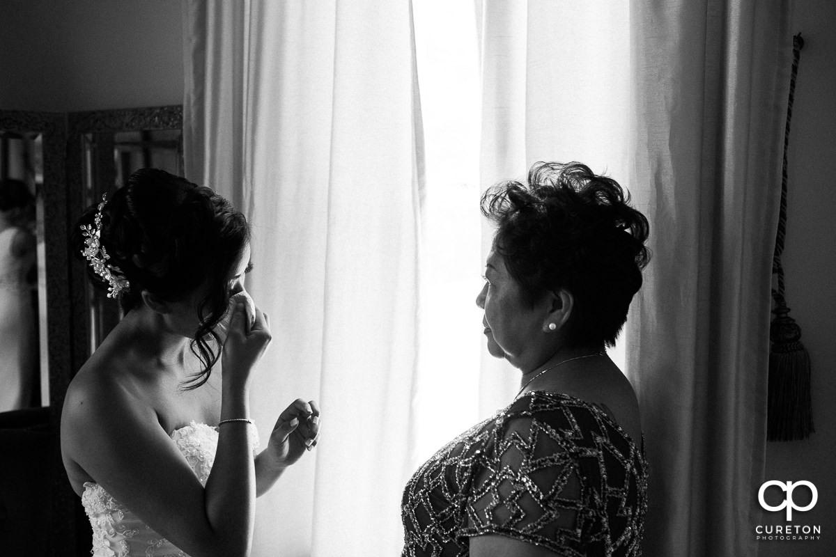 Bride tearing up as she is getting ready with her mother.