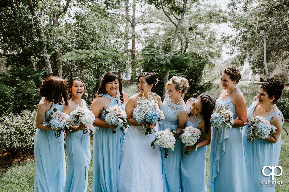 Bride and bridesmaids laughing with each other.