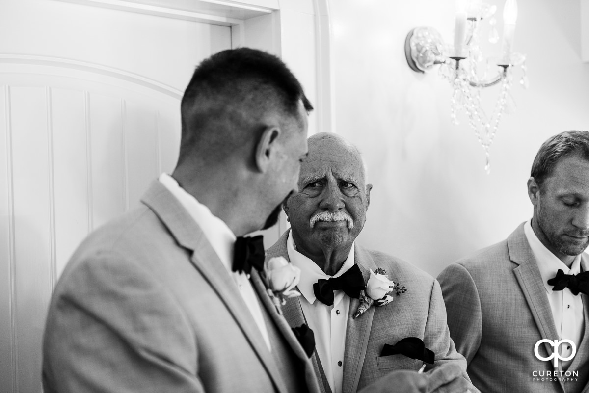 Groom's father looking on as his son is receiving a gift before the wedding ceremony.
