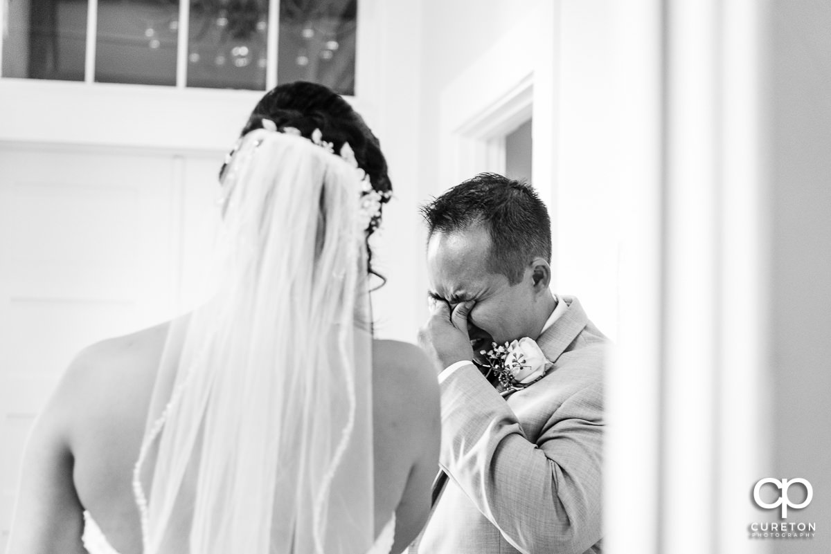 Bride's brother crying when he sees his sister in her dress for the first time before the ceremony.