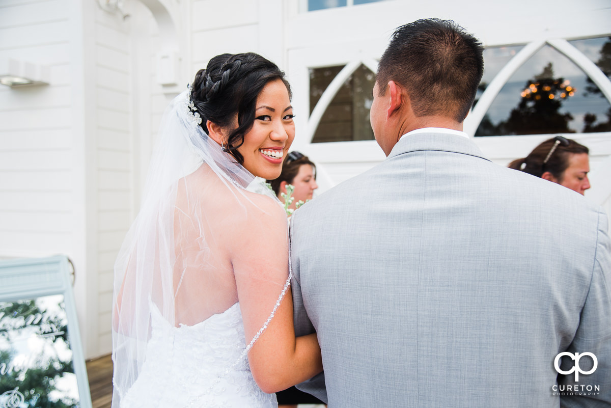 Bride smiling before she is walking down the aisle.