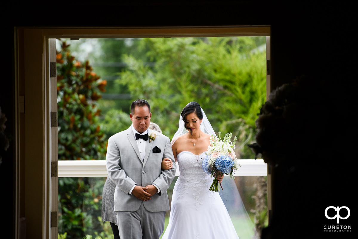 Bride and her brother walking down the aisle at the wedding ceremony.