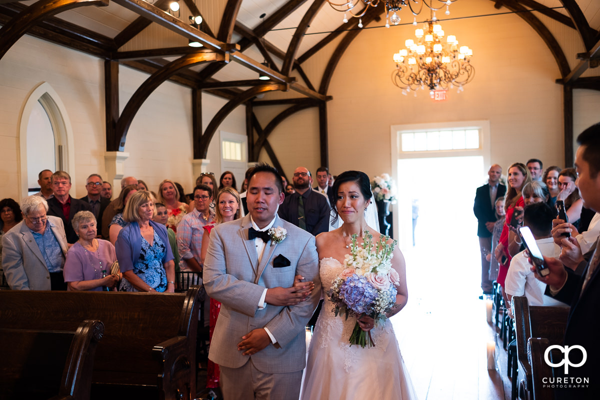 Bride and her brother walking down the aisle at the wedding ceremony at the Tybee Island Wedding Chapel.